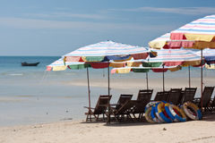 Tropical beach rental. Beach chairs and umbrellas for rent on tropical beach Royalty Free Stock Image
