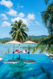 Tropical beach resort with clear water swimming pool. With beach umbrellas and chairs near the sea Stock Photo