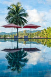 Tropical beach resort with clear water swimming pool. With beach umbrellas and chairs near the sea Stock Photography