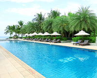 Tropical beach resort hotel swimming pool. Tropical beach vacation and travel concept Royalty Free Stock Photo