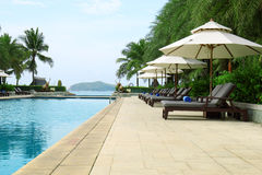 Tropical beach resort hotel swimming pool. Tropical beach vacation and travel concept Stock Images