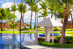 Tropical beach resort with umbrellas and lounge chairs Royalty Free Stock Images