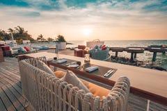 Moody beach resort restaurant in sunset light. Minimalist table set-up Stock Photography