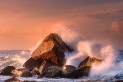 Tropical beach with rocks and big crashing waves. At sunset Mirissa, Sri Lanka Stock Photo