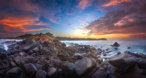 Tropical beach with rocks on sand coast of ocean. Tropical beach with rocks on sand coast of the ocean at sunset Mirrisa, Sri Lanka Stock Image