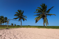 Tropical beach with rustic goal, palm trees, white sand and pure Royalty Free Stock Photos