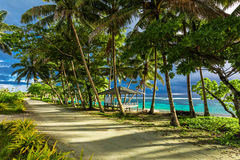 Tropical beach on Samoa Island with palm trees and dirt road. South of Upolu Royalty Free Stock Photos