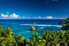 Tropical beach on Samoa Island with palm trees on small island, stock photo