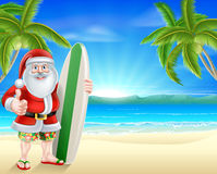 Tropical beach Santa. Cartoon Santa holding a surfboard and giving a thumbs up in his board shorts and sandals on a beach with palm trees in the background Stock Photography