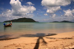 Tropical beach scene. Boat moored at a tropical beach with a palm tree shadow Stock Photography