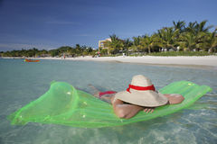 Tropical Beach Scene. Pretty woman lying in shallow water by a tropical beach Stock Photos