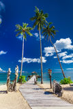 Tropical beach scene with coconut palm trees and jetty, South Pa. Cific islands, Samoa Royalty Free Stock Image