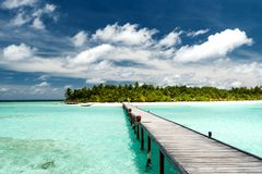 Tropical beach scenery. With wooden jetty leading to a beautiful island Royalty Free Stock Photo
