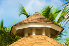 Tropical beach shelter roof and palm tree basking in hot sunshine. Royalty Free Stock Photo