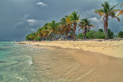 Tropical beach before storm. Tropical beach on a Caribbean island before storm, color and contrast modified for more dramatical result Royalty Free Stock Images