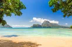 Tropical beach with lush green islands in the backgroud. Tropical beach in the sun Stock Images