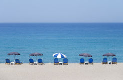 Tropical beach with sunbeds. Beach at the Greek ionian island Lefkada with parasols Royalty Free Stock Image