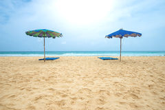 Tropical beach with sunbeds and umbrella Stock Images