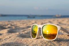 Tropical Beach Sunglasses. Sunrise on a tropical beach reflected in a pair of sunglasses Stock Photo