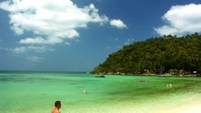 Tropical beach in sunny day on the island, woman. Floating on the depth, some snorkeling people and walking man. Footage stock footage