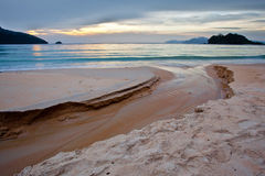 Tropical beach and sunset. A small stream clowing through a beach in Langkawi, Malaysia at sunset Royalty Free Stock Photography