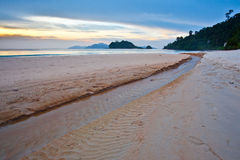 Tropical beach and sunset. A small stream clowing through a beach in Langkawi, Malaysia at sunset Stock Photos