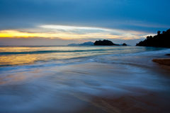 Tropical beach and sunset. A small stream clowing through a beach in Langkawi, Malaysia at sunset Stock Photo