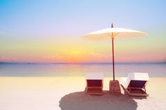Tropical beach in sunset with beach chairs and umbrella Royalty Free Stock Photos