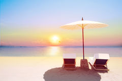 Tropical beach in sunset with beach chairs and umbrella Royalty Free Stock Photography