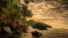 Tropical beach sunset in Costa Rica. Sunset on the shore in Manuel Antonio Costa Rica with crashing Royalty Free Stock Photo