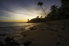Tropical beach at sunset. Wave laps the shore on tropical beach during sunset Stock Photography