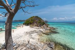 Tropical beach with tourists and boats on the island Bulog Dos. Palawan, Philippines. Beautiful tropical island with sand beach, palm trees.  Travel concept Royalty Free Stock Photography