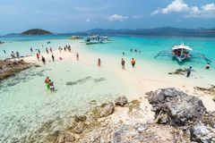 Tropical beach with tourists and boats on the island Bulog Dos. Palawan, Philippines. Beautiful tropical island with sand beach, palm trees.  Travel concept Stock Photo