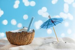 Tropical beach or travel concept: summer cocktail in coconut and sun umbrella royalty free stock photography