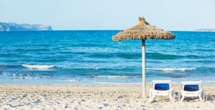 Tropical beach with umbrella and sun loungers Royalty Free Stock Images
