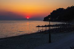 Tropical beach umbrellas, sun and colorful sunset sky Stock Images