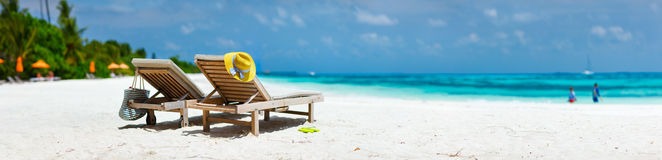 Tropical beach vacation. Panorama of lounge chairs on a beautiful tropical beach at Maldives Royalty Free Stock Images