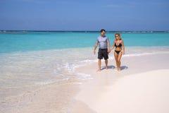 Tropical beach walk. A couple walking along a beautiful tropical beach shoreline Stock Image