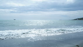 Tropical beach waves with a cloudy sky. In background stock video
