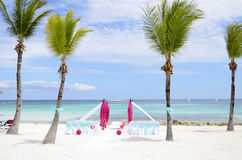Tropical Beach Wedding Ceremony Setup. Pretty cerise pink and aqua theme beach wedding ceremony scene with chairs and gazebo setup on the beach between the palm Royalty Free Stock Photos