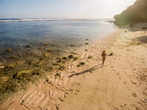 Tropical beach with a woman running. Aerial view of tropical beach with a woman running. Female in bikini running on the sea shore Stock Photo