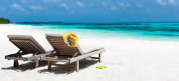 Tropical beach. Wooden lounge chairs and a yellow straw hat on a beautiful tropical beach at Maldives Stock Photography