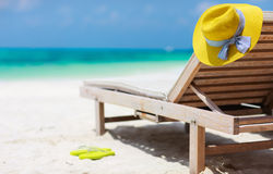 Tropical beach. Wooden lounge chairs and a yellow straw hat on a beautiful tropical beach at Maldives Royalty Free Stock Image