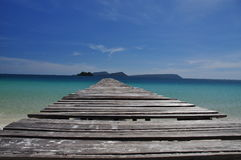 Tropical beach and wooden pier, Koh Rong island, Cambodia. Koh Rong island, Cambodia. White sand tropical beach, wood pier and turquoise ocean Royalty Free Stock Image