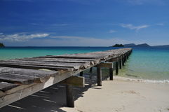 Tropical beach and wooden pier, Koh Rong island, Cambodia. Koh Rong island, Cambodia. White sand tropical beach, wood pier, deep blue and turquoise ocean Stock Photos