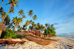 Tropical beach. Wooden sailboat  (dhow) and palm trees on a tropical beach of Zanzibar island Royalty Free Stock Images