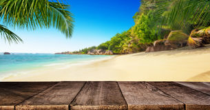 Tropical beach with wooden table, summer holiday background. Royalty Free Stock Images