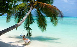Tropical beach. Young woman relaxing on a swing hanging on a palm at tropical white sand beach at Maldives Stock Image