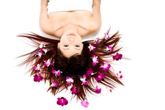 Tropical Beauty. A young Asian woman lying on the floor with purple orchid flowers Stock Images
