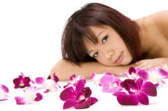 Tropical Beauty. A young Asian woman lying on the floor with purple orchid flowers Stock Photo
